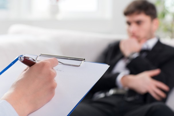 Psychologist-taking-notes-on-a-male-patient