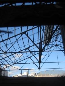 Telas de araña, vigas y cerchas sobre el cielo del barrio.