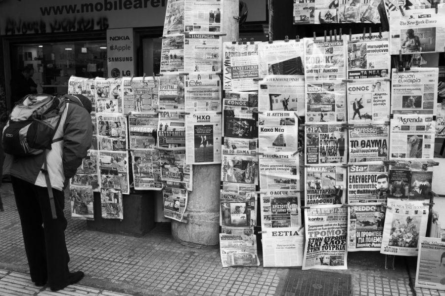 Un homme se penche pour choisir parmi des magazines pornographiques, délaissant les unes des journaux sérieux