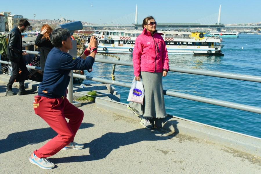 Un homme asiatique plie les genoux pour photographier sa compagne, qui pose au bord de l'eau à Istanbul