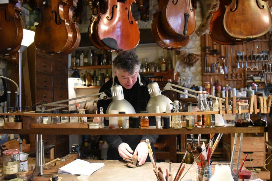 un homme fabrique des violons