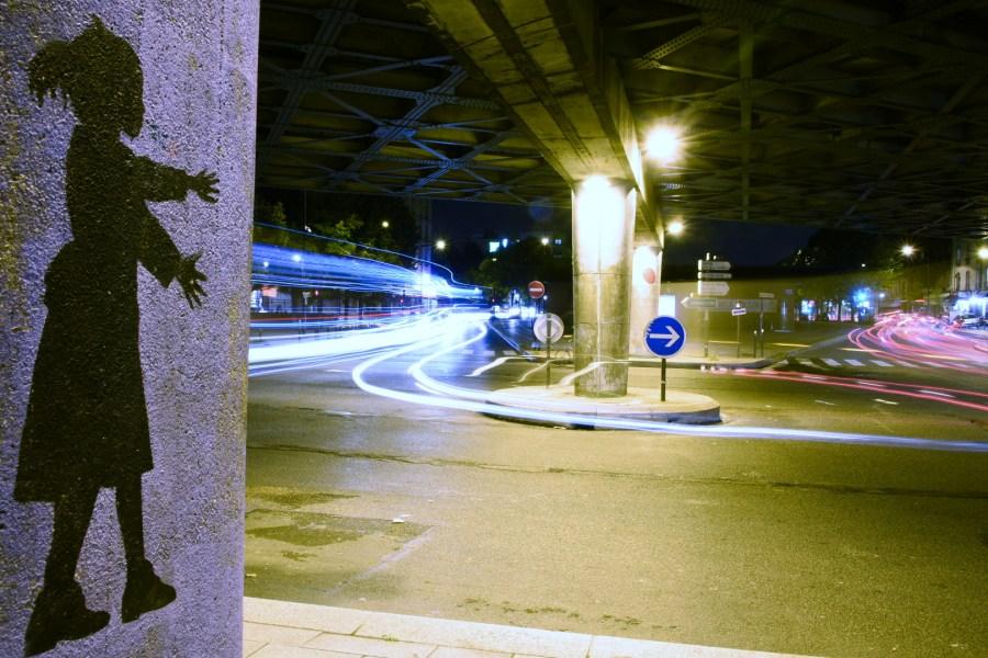 Circulation automobile de nuit, sous un pont autoroutier, avec un rond-point et un graffiti représentant une petite fille