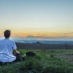 man next to lake meditating
