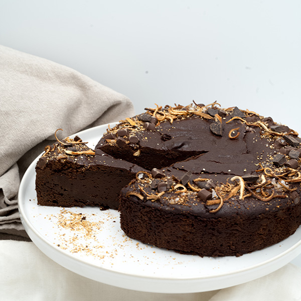 orange flavored chocolate brownie cake with a slice cut out of it