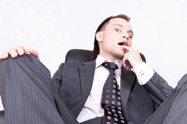 指をくわえた挑発的態度のビジネスマン