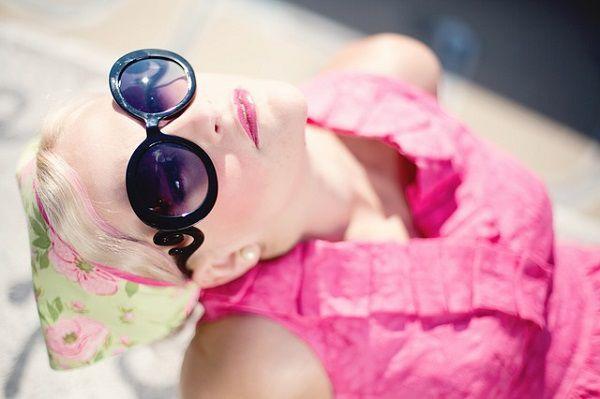 空を見上げるサングラスの女性