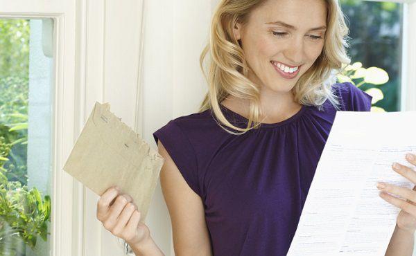 お見合い会社からの封筒を開けるアラサー女性