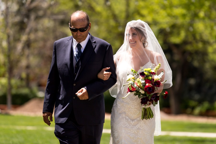 Gina and her father walk down the aisle during an Our Lady of Lourdes Denver wedding.