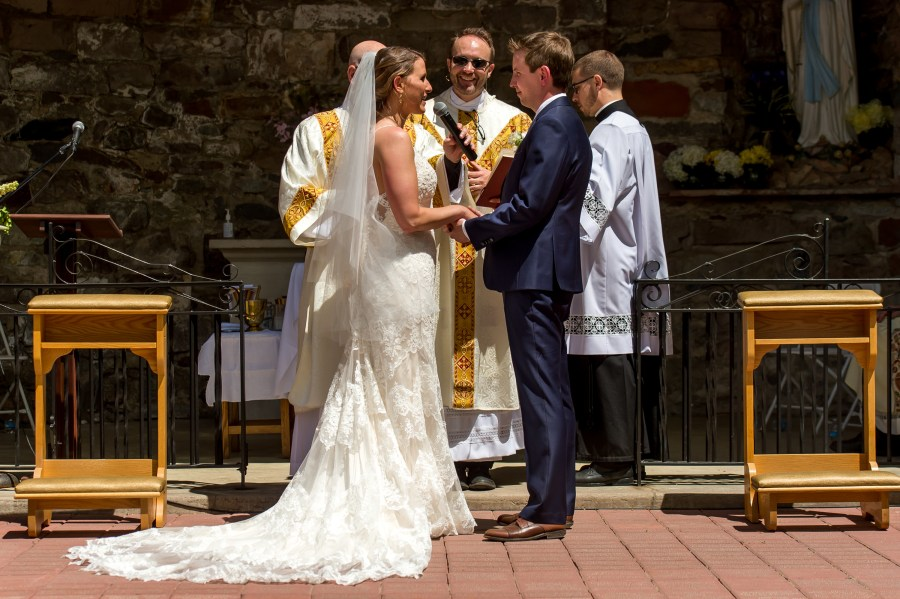 Exchanging vows during an Our Lady of Lourdes Denver wedding.