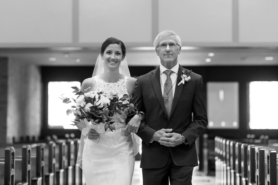 Father walks bride down the aisle at Our Lady of Lourdes Catholic Church in Denver, Colorado