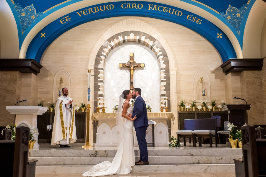 Bride and groom kiss at a Catholic wedding Mass at Our Lady of Lourdes Catholic Church in Denver, Colorado.