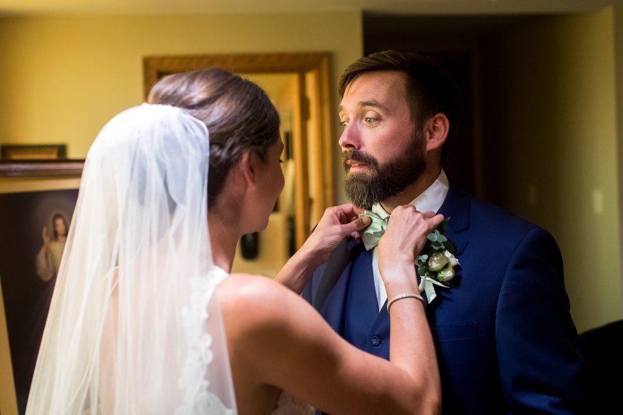 Bride adjusts groom's bow after a wedding Mass at Our Lady of Lourdes Catholic Church in Denver, Colorado.