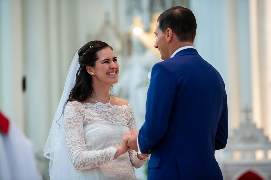Bride smiles at groom during their wedding at the Cathedral Basilica of the Immaculate Conception in Denver, Colorado.