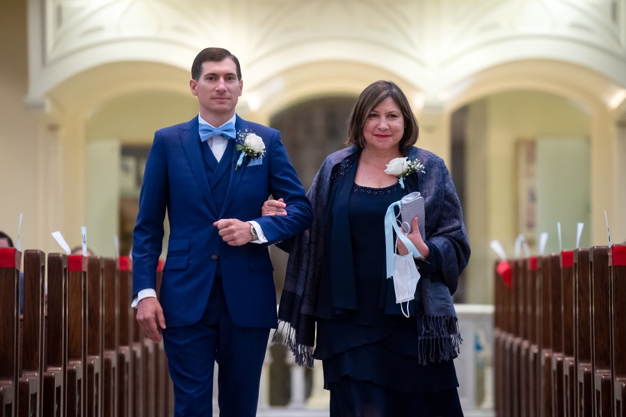 Groom processes in with his mother at his wedding at the Cathedral Basilica of the Immaculate Conception in Denver, Colorado.