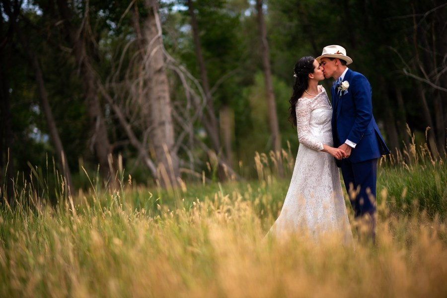Bride and groom kiss during their wedding portrait session at Bear Creek Lake Park in Lakewood, Colorado.
