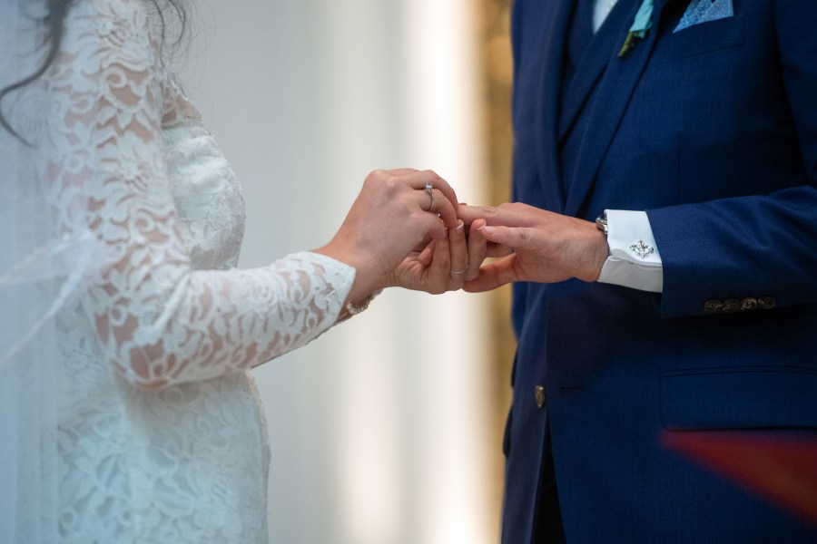 Bride puts a ring onto the groom's finger during their wedding at the Cathedral Basilica of the Immaculate Conception in Denver, Colorado.