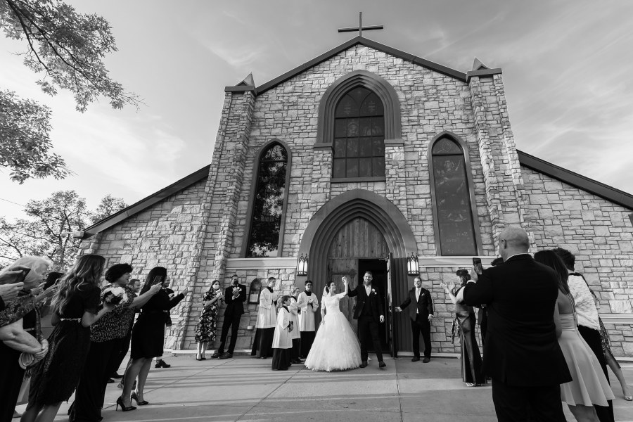 Bride and groom walk outside the church after a wedding at Our Lady of Mt. Carmel in Littleton, Colorado.