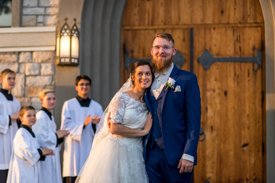 Bride and groom react outside the church after a wedding at Our Lady of Mt. Carmel in Littleton, Colorado.