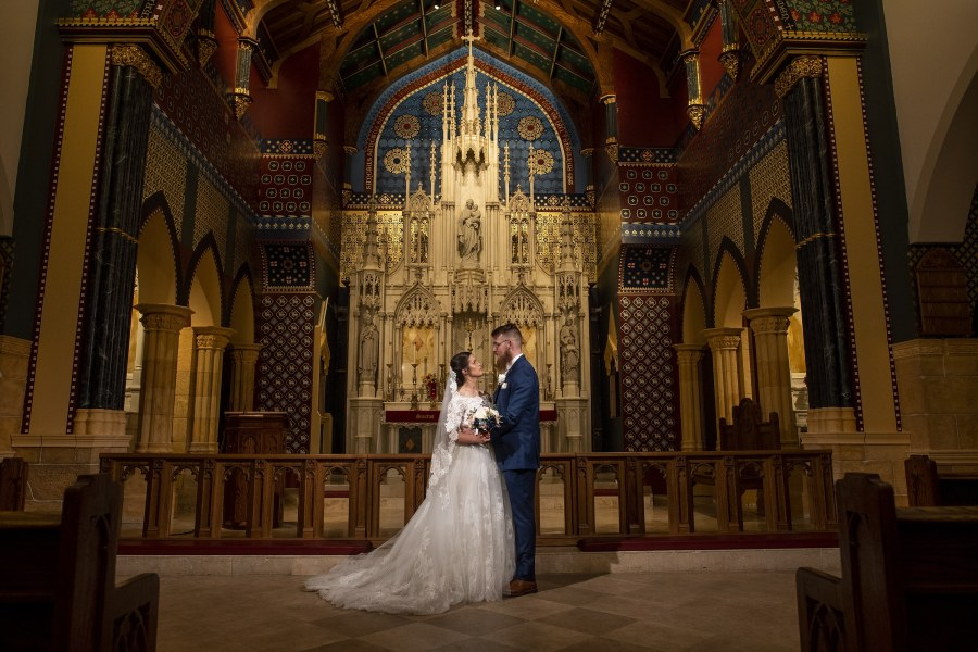 Bride and groom pose inside the church after a wedding at Our Lady of Mt. Carmel in Littleton, Colorado.