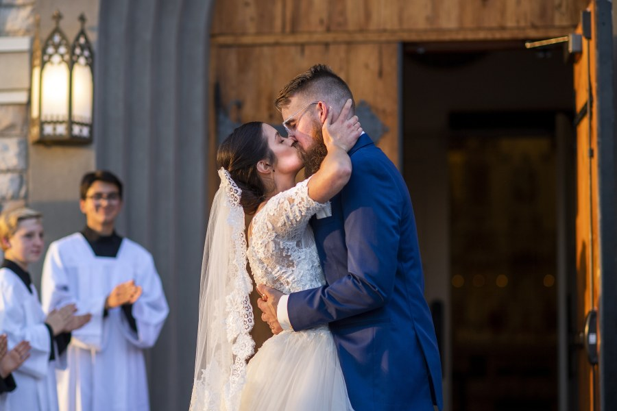 Bride and groom kiss after a wedding at Our Lady of Mt. Carmel in Littleton, Colorado.