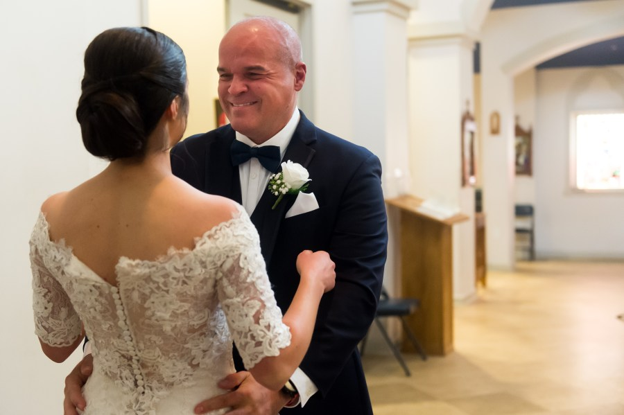 The father of the bride reacts before his daughter's wedding at Our Lady of Mt. Carmel in Littleton, Colorado.
