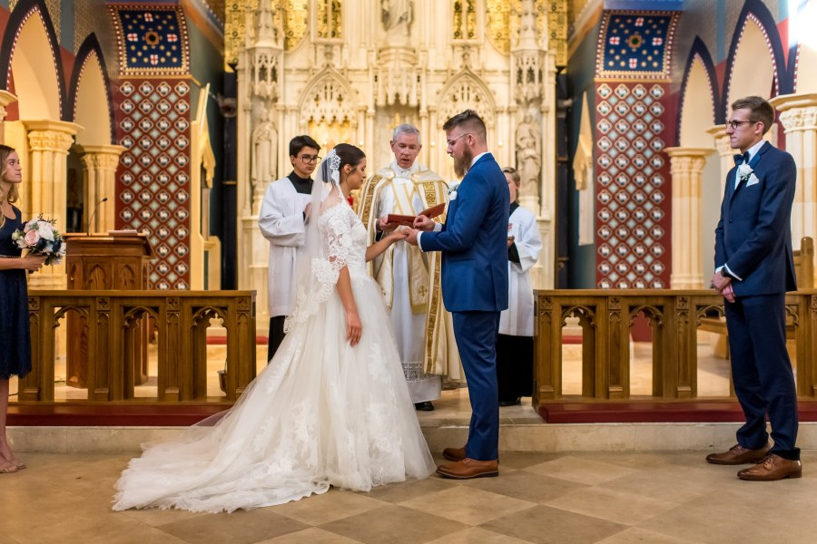 Groom puts on the ring at Our Lady of Mt. Carmel in Littleton, Colorado.