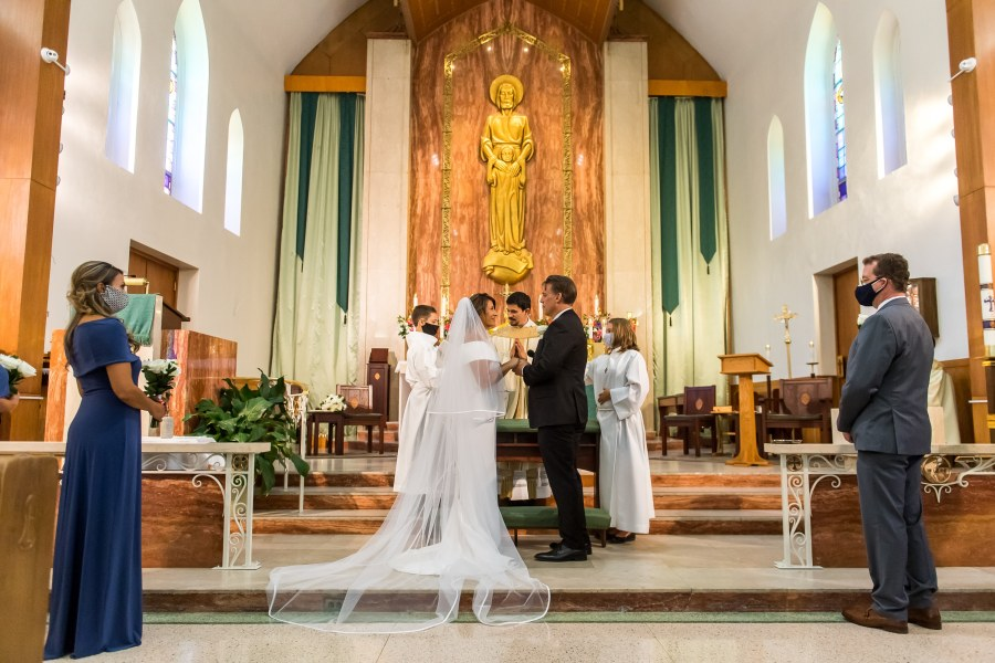 The bride and groom say their wedding vows during a wedding Mass at St. Joseph Catholic Church in Fort Collins, Colorado, on August 8, 2020.