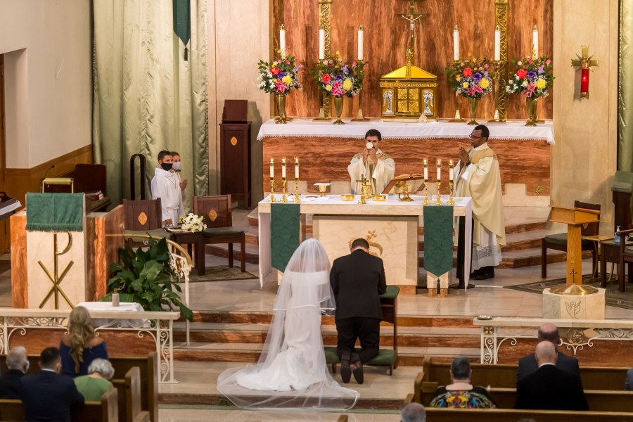 The priest holds up the consecrated host during a St. Joseph Catholic Church wedding on August 8, 2020, in Fort Collins, Colorado.
