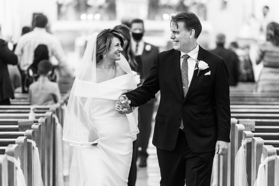 Bride and groom smile walking down the aisle during their St. Joseph Catholic Church wedding on August 8, 2020, in Fort Collins, Colorado.