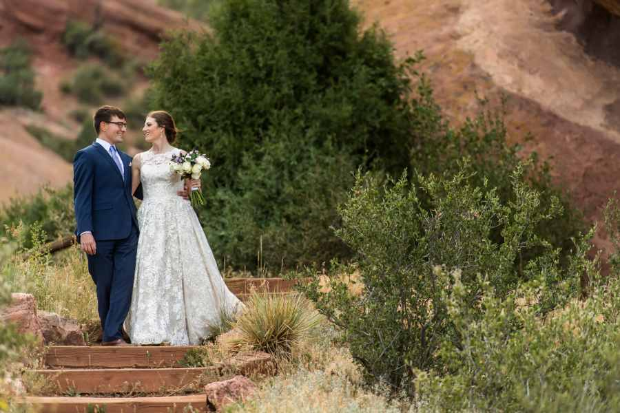 Bride and groom look at each other during Red Rocks wedding photos at Red Rocks Park and Amphitheater in Denver, Colorado, with Stacy and Andrew.