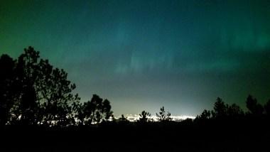 northern lights above trondheim city in bymarka
