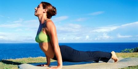 Woman doing yoga near coast