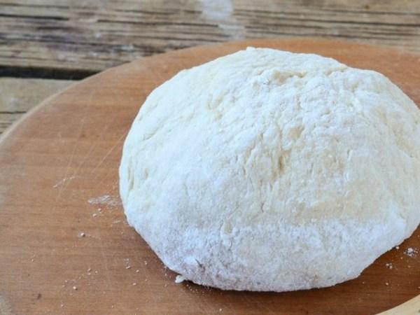 Возьмите глубокую миску, затем через мелкое ситце просейте в нее пшеничную муку, добавьте два сырых яйца и соль. Влейте теплую воду и вымесите крутое тесто. Выложите его на ровную рабочую поверхность, подсыпайте понемногу муку и выместите тугое тесто, чтобы оно не липло к рукам.