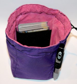 Inside, there's a strap to keep your stat cards, or spell cards if you play Warhammer Fantasy. It will easily hold 20 Warmachine cards in plastic slip pockets.