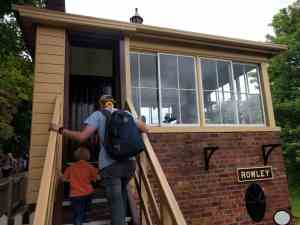 Father and son climbing stairs to look at a train signal box