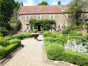 Country farm house with formal gardens on a sunny day