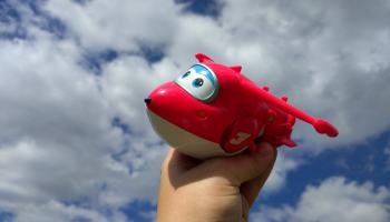Red toy plane against blue and cloudy sky