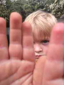 A boy with his hands out partially blocking his face