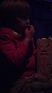 Poor picture of boy eating popcorn at the cinema