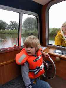 Boy in life jacket at the captain's seat on a boat