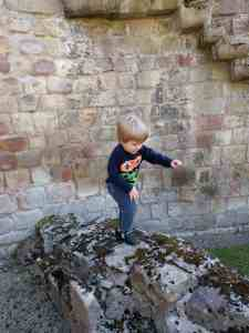 Prudhoe Castle Small boy balancing on wall