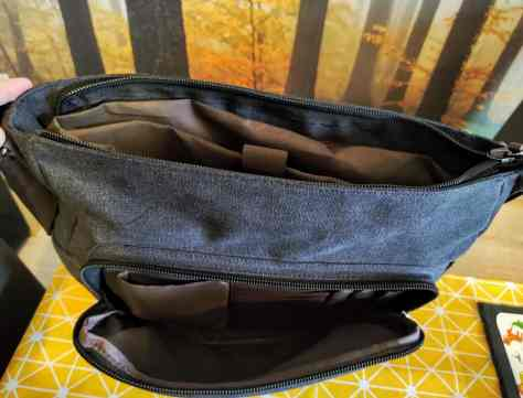 open satchel showing laptop pouch and front pocket with space for pens etc