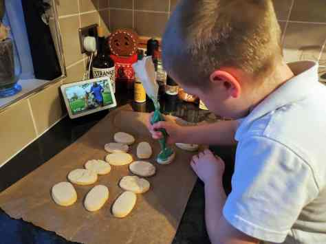 Boy icing biscuits
