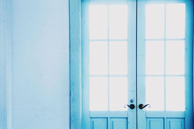 日差しが差し込む青いドア