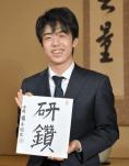 笑顔で色紙を持った藤井聡太の画像