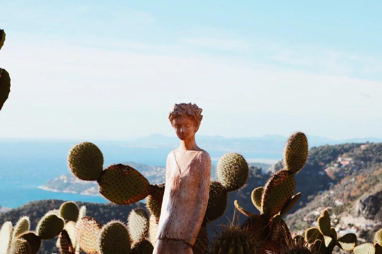 Escultura, cactus e a costa azul ao fundo