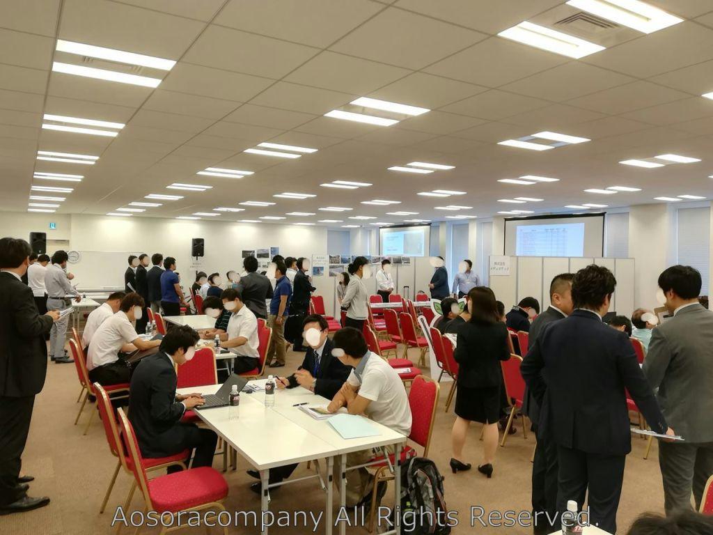 ご覧のように会場は参会者の熱気でいっぱいでした。(笑) 左手側のテーブルが商談席、右手側が各社のセミナーブースにっています。
