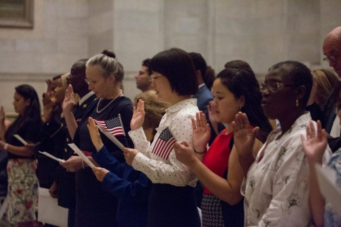 Image of naturalized U.S. citizens taking the oath of allegiance at the Naturalization Ceremony