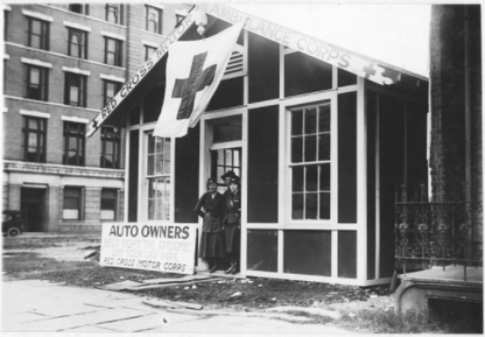 Black and white photograph of two women outside a building with an American Red Cross sign.