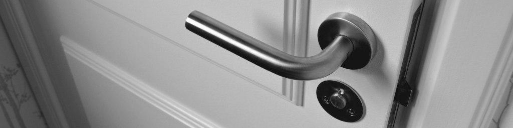 Fechadura de prata instalada em uma porta branca.